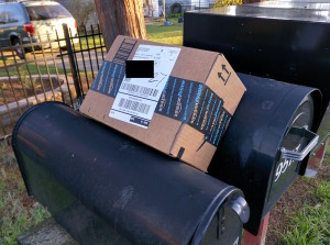 Package left by USPS carrier on top of mailboxes